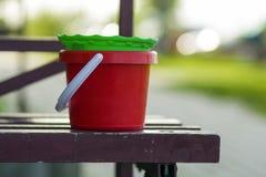 塑料婴孩玩具红色和绿色桶特写镜头在老棕色长木凳的在被弄脏的明亮的夏天bokeh背景 孩子f 图库摄影