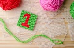 塑料帆布,手工制造与在木backgro的红色毛线数字 库存照片
