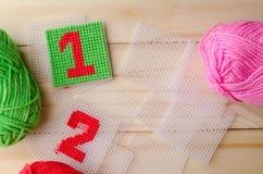 塑料帆布,手工制造与在木backgro的红色毛线数字 免版税库存图片