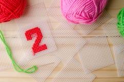 塑料帆布,手工制造与在木backgro的红色毛线数字 免版税库存照片