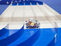 塑料式样运行在车道轨道的标度微型赛车 免版税库存图片