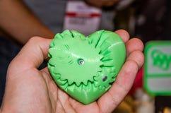 塑料心脏在他的包括齿轮的手上在3D打印机打印了 库存图片