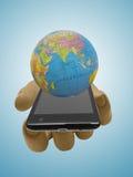 塑料时装模特玩偶的手有智能手机和地球地球的 免版税图库摄影