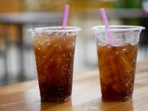 塑料杯子杯可乐可乐或焦炭在木桌上休息 免版税库存照片