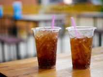 塑料杯子杯可乐可乐或焦炭在木桌上休息 库存照片