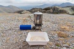 塑料杯子用等待在一个金属杯子的燕麦粥一会儿在与集气筒的一个便携式的火炬将煮沸水 免版税库存照片