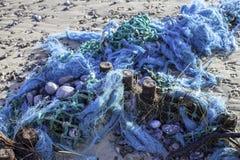 塑料污染-蓝色缠结了在b洗涤的捕鱼网 免版税库存图片