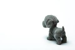 塑料玩具在轻的背景的一条狗 库存图片