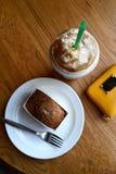 塑料玻璃用在一个咖啡馆和一个蛋糕的一份冷的咖啡在一张木桌和一个黄色钱包上的一块板材 库存照片