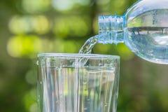 塑料瓶倾吐的水到在绿色模糊的backgr的一块玻璃里 免版税库存图片