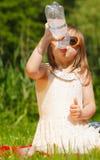 从塑料瓶的小的渴女孩儿童饮料水,室外 库存照片