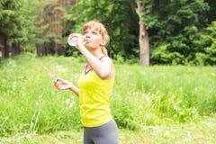 从塑料瓶的少妇饮用水在跑步以后 丢失重量 健康生活方式 图库摄影