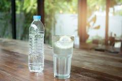 塑料瓶装水和玻璃用切片柠檬和冰块 免版税库存图片