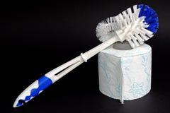 塑料白色蓝色洗手间刷子和纸 免版税库存照片
