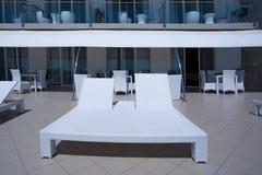 塑料白色sunbeds的特写镜头图片在一家别致的旅馆的大阳台的在海滩附近的 夏天背景概念 免版税库存图片