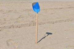 从塑料的蓝色铁锹与孩子的木尾巴在a的沙子 图库摄影