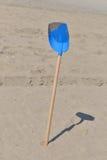从塑料的蓝色铁锹与孩子的木尾巴在a的沙子 库存照片