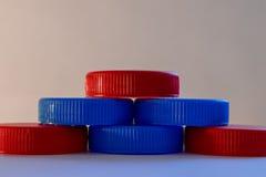 塑料盖子是红色和蓝色,被建立入金字塔 库存图片