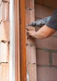 塑料窗口设施 工作者操练螺丝的一个孔 免版税库存图片