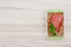 塑料膳食预习功课容器用煮沸的荞麦粥和s 库存照片