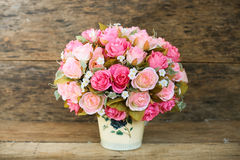 塑料花有在葡萄酒图片样式的木背景,家内部设备,花在木背景设置了 免版税库存照片