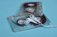塑料透明卡型盒式录音机和白色真空耳机在明亮的蓝色背景 免版税库存图片