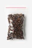 塑料透明拉链袋子用在白色隔绝的充分的整粒咖啡豆,与红色夹子的真空包装大模型 概念 免版税图库摄影