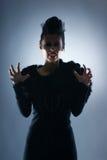 塑造一个女性吸血鬼的射击一件黑暗的礼服的 免版税图库摄影