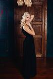 塑造一个富有的内部魅力美丽的年轻白肤金发的女孩,有白肤金发的卷发的一名妇女的照片在典雅的黑色 库存图片