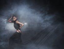 塑造一个少妇的射击一件黑礼服的 库存图片