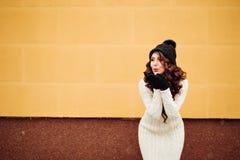 塑造一个相当滑稽的女孩的生活方式画象,黑行家帽子,自然构成,白色被编织的毛线衣 亲吻发送 库存图片