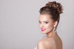 塑造一个美丽的可爱的女孩的画象有一个高柔和的典雅的晚上婚礼的发型和明亮的构成的与流程 免版税库存照片