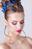 塑造一个美丽的可爱的女孩的画象有一个高柔和的典雅的晚上婚礼的发型和明亮的构成的与流程 免版税库存图片