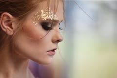 塑造一个美丽的女孩的画象有幻想的金黄m 免版税库存照片