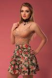塑造一个美丽的少妇的照片俏丽的衣裳的有摆在桃红色背景的花的 床单方式放置照片诱人的白人妇女年轻人 免版税库存图片