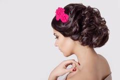 塑造一个美丽的性感的逗人喜爱的浅黑肤色的男人的画象有美好的时髦的理发、明亮的构成和花的在她的头发 免版税库存图片