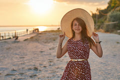 塑造一个年轻美丽的女孩的画象一件礼服的有拿着秸杆海滩帽子的鸟样式的 免版税库存照片