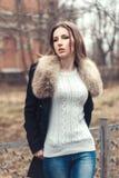 塑造一名美丽的妇女的街道画象皮大衣的 库存图片