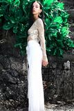 塑造与在摆在岩石和绿色热带异乎寻常的叶子背景附近的宽腿经典裤子的黑暗的长的头发 免版税图库摄影