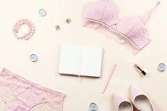 塑造与妇女典雅的桃红色鞋带胸罩的博客作者工作区和内裤、泵浦和笔记本 时髦的女用贴身内衣裤舱内甲板位置 库存图片