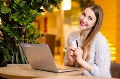塑造与白肤金发的长的头发和明亮的桃红色唇膏在白色毛线衣坐一把椅子在一个咖啡馆与美好的时髦的内部 免版税库存照片