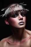 塑造与金属headwear的秀丽模型和在黑背景的发光的银色红色构成和蓝眼睛和红色眼眉 库存图片