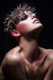 塑造与金属headwear的秀丽模型和在黑背景的发光的银色红色构成和蓝眼睛和红色眼眉 免版税图库摄影