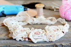 塑造与鞋带修剪和小珠的纺织品项链 胶合热的枪,剪刀,螺纹,在木桌上的毛毡 夏天花卉首饰 免版税库存图片