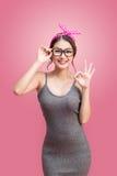 塑造亚裔女孩画象有站立在桃红色的太阳镜的 库存图片