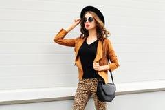 塑造佩带一个减速火箭的典雅的帽子、太阳镜、棕色夹克和黑提包的俏丽的妇女走在背景的城市 免版税库存图片