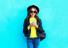 塑造使用智能手机的俏丽的妇女在五颜六色的蓝色的佩带的黑色岩石样式衣裳 免版税库存图片