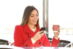 塑造使用智能手机的妇女在咖啡店 免版税库存照片