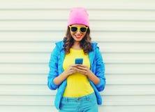 塑造使用智能手机的愉快的凉快的微笑的女孩在戴桃红色帽子黄色太阳镜的白色背景的五颜六色的衣裳 免版税库存图片