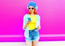 塑造使用有一个咖啡杯的微笑的妇女智能手机在五颜六色的桃红色 免版税库存照片
